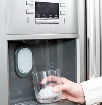 Ein Glas Wird Von Einem Kühlschrank Mit Eiswürfel Befüllt.